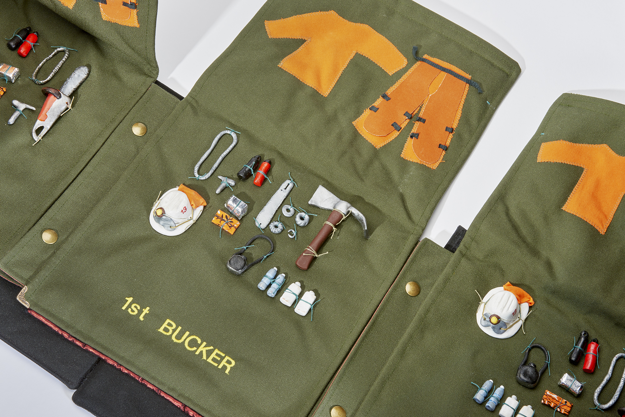 """Kim Abeles and the Firefighting Women of Camp 13 / Valise 2 - Tools from the series, Valises for Camp Ground: Arts, Corrections, and Fire Management in the Santa Monica Mountains 2018 Hand constructed """"backpack"""" valise made with Cordura, Velvet, Clay miniatures of firefighting tools, Embroidered names of each position on a fire crew, brass hardware  Size: Closed: 23"""" x 10"""" x 14""""   Open: 10"""" x 167"""" x 22"""" This inaugural Camp Ground project with inmates from Camp 13 was managed by the Armory Center for the Arts, with Kim Abeles as the first commissioned artist. Camp Ground: Arts, Corrections, and Fire Management in the Santa Monica Mountains is made possible by the National Endowment for the Arts and the Los Angeles County Arts Commission."""