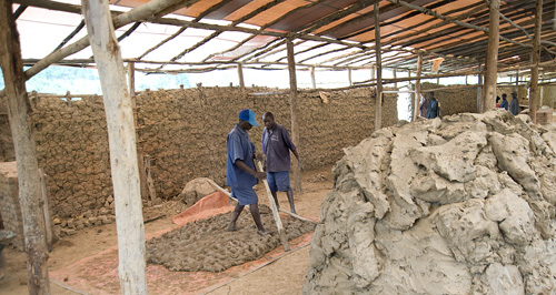 On the right, a large pile of mined clay awaits processing. On the left, a TIG member works the clay with his feet.