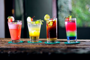 tropical mixed drinks with fruit in various colors