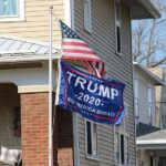 American Flag And Trump 2020 Flag On Pole In Front Of House