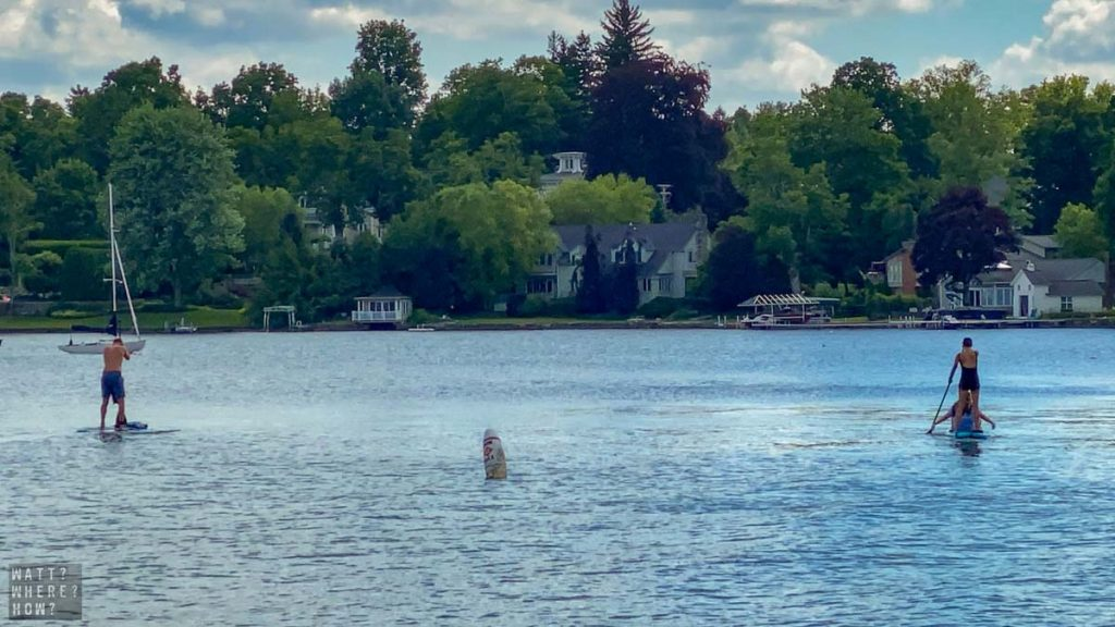 standup paddleboarders enjoy the relaxed lifestyle of Skaneateles Lake New York.