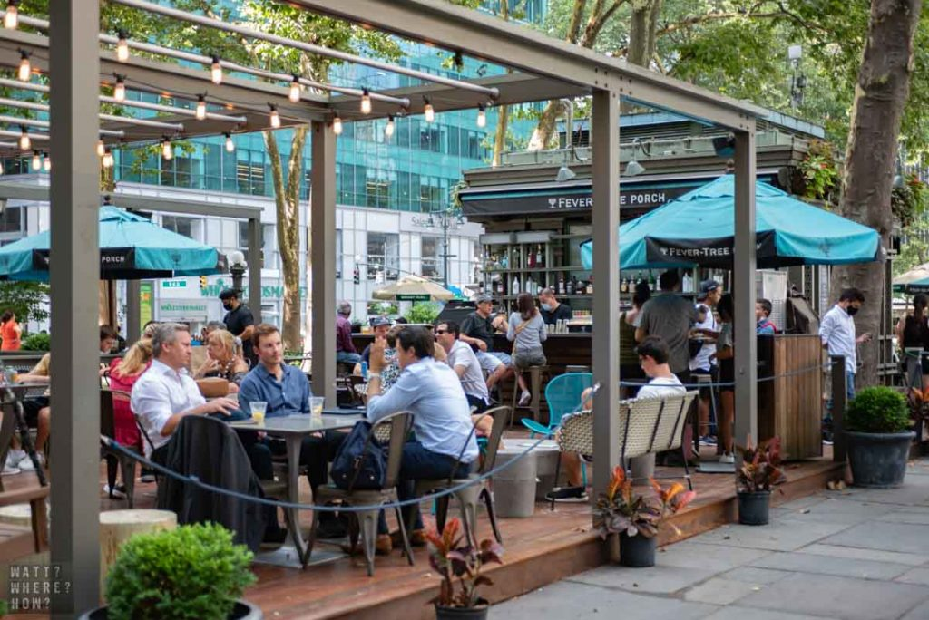 Fever-Tree Porch at Bryant Park NY is an open wooden deck with tables and swing loveseats.