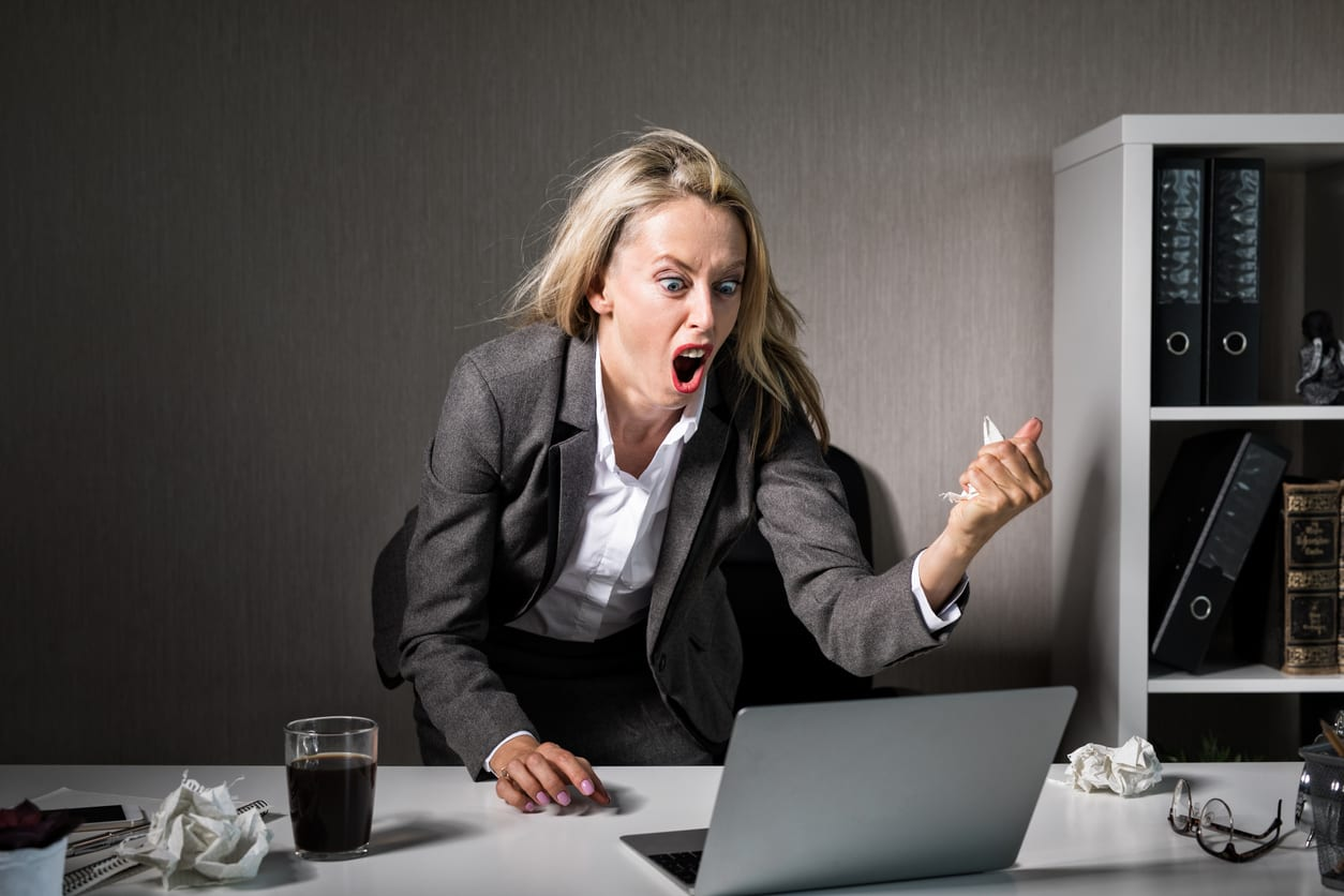 woman yelling furiously at her laptop