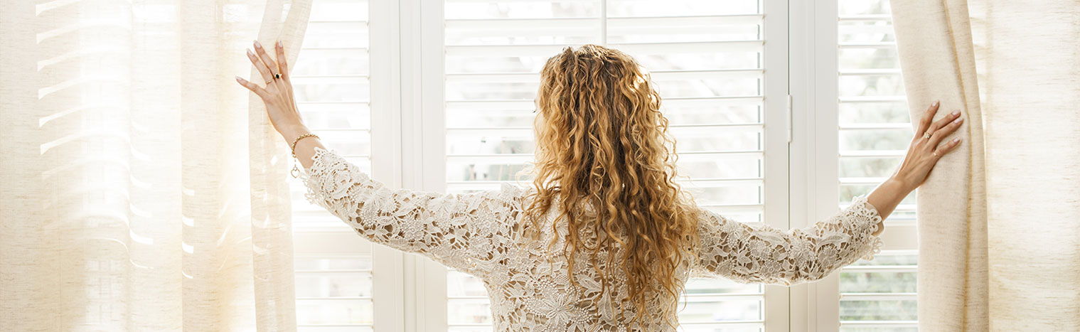 Woman looking out big bright window with blinds