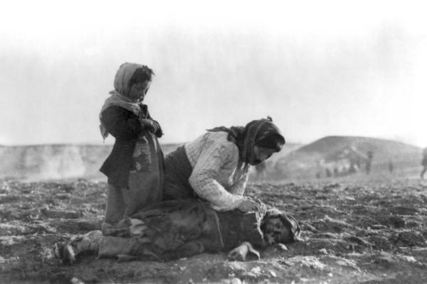 Une femme arménienne s'agenouant auprès d'un enfant décédé durant le génocide arménien.