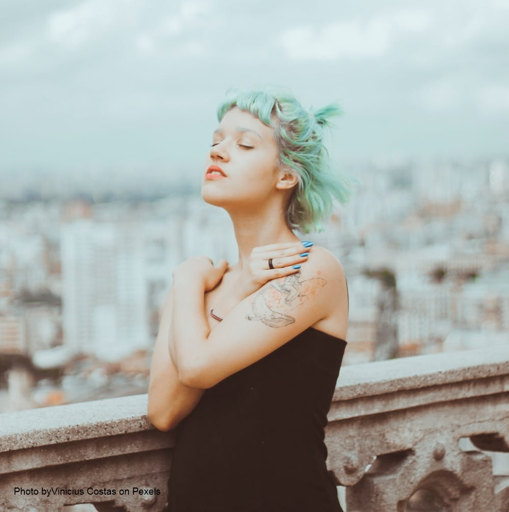 Woman with green hair on balcony hugging herself represents personal boundaries.