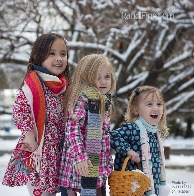 Three young sisters standing my snow covered tree smiling representing triangulation.