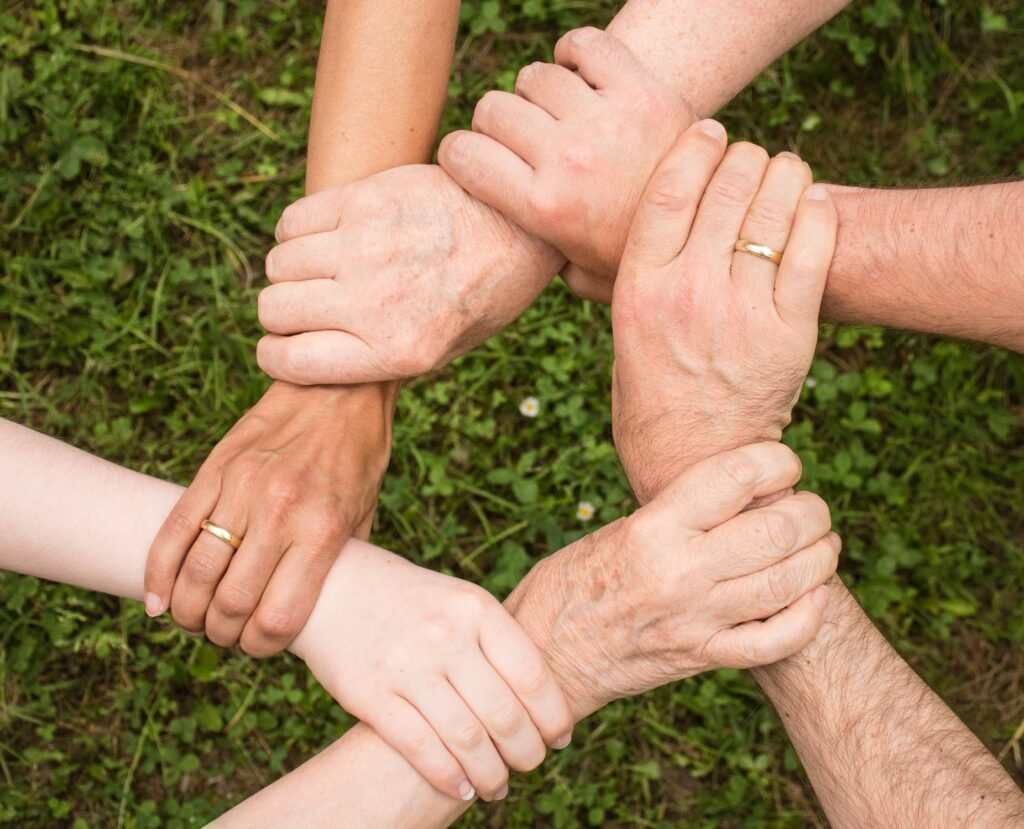 Image of enmeshed family joining hands