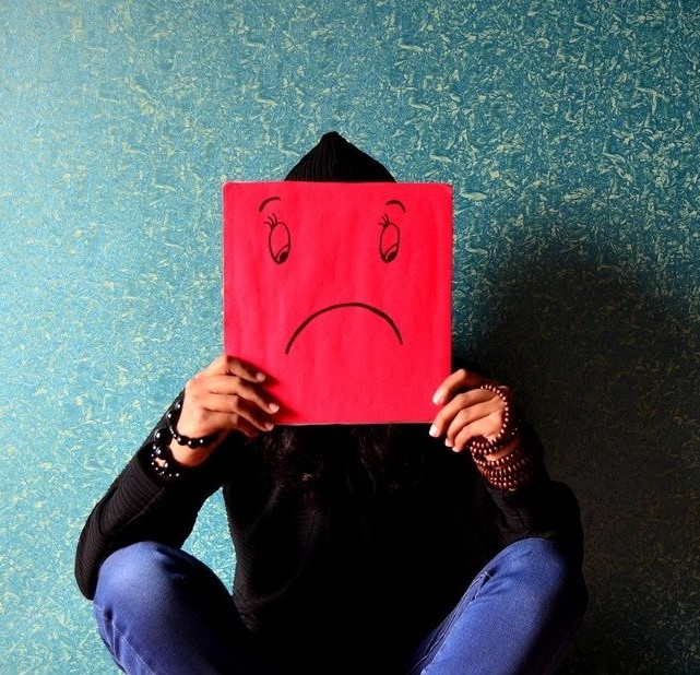 Image of person holding red paper with sad face drawn representing toxic emotions