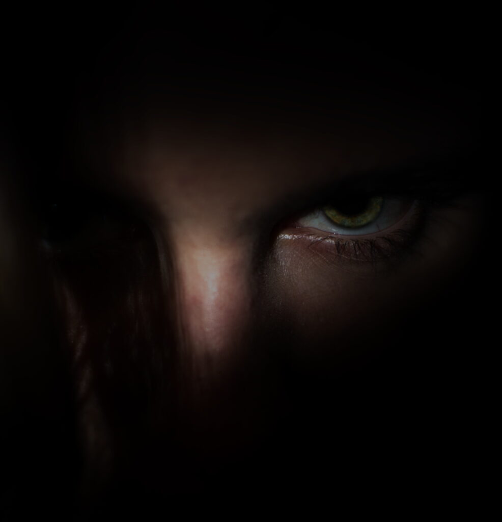 evil eye of sociopath surrounded by darkness