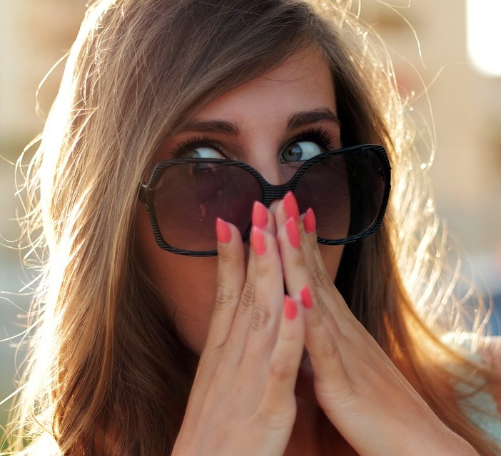 Woman with sunglasses and red nail polish experiencing synchronicity