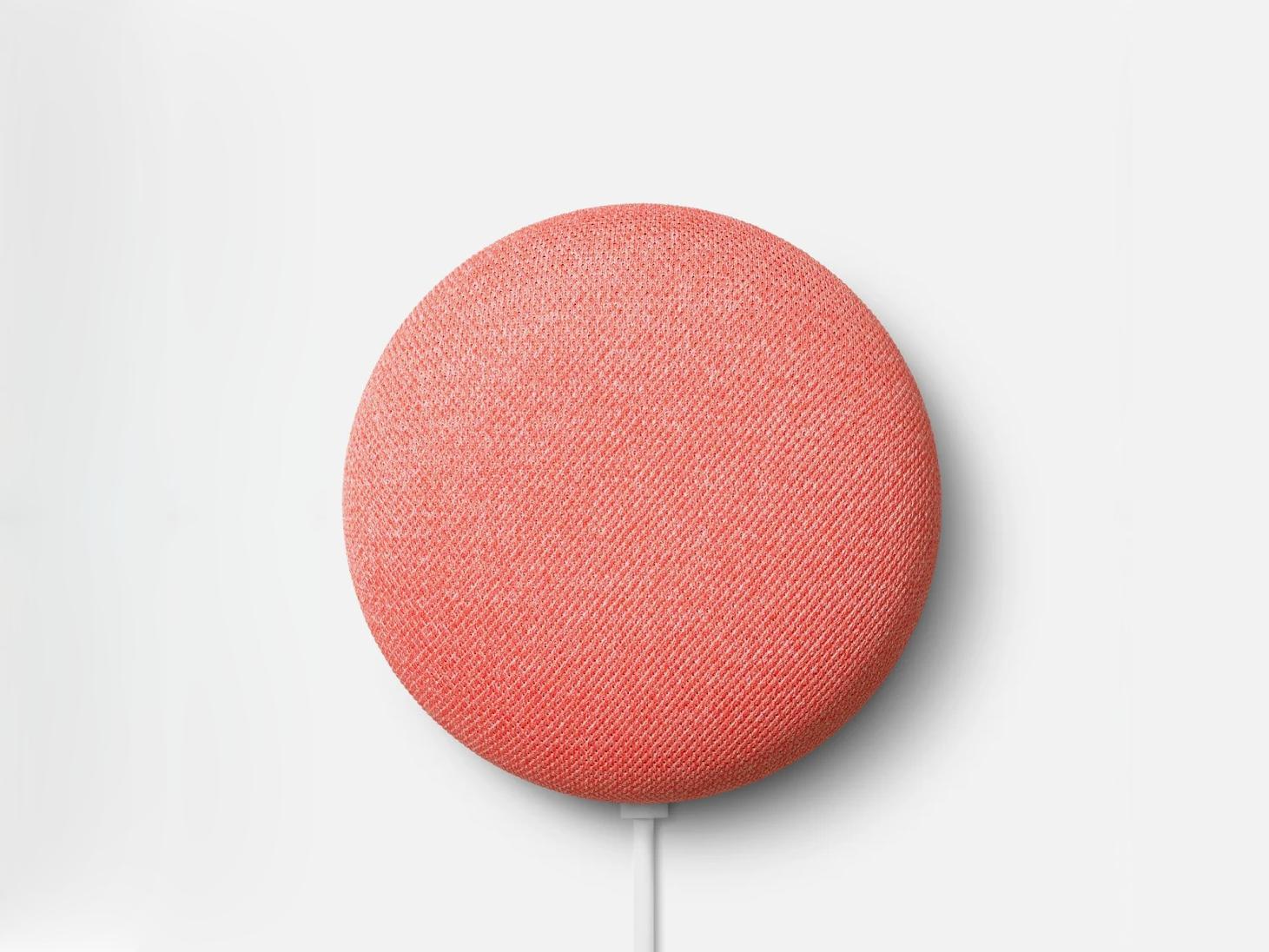a pink round nest mini speaker on white background