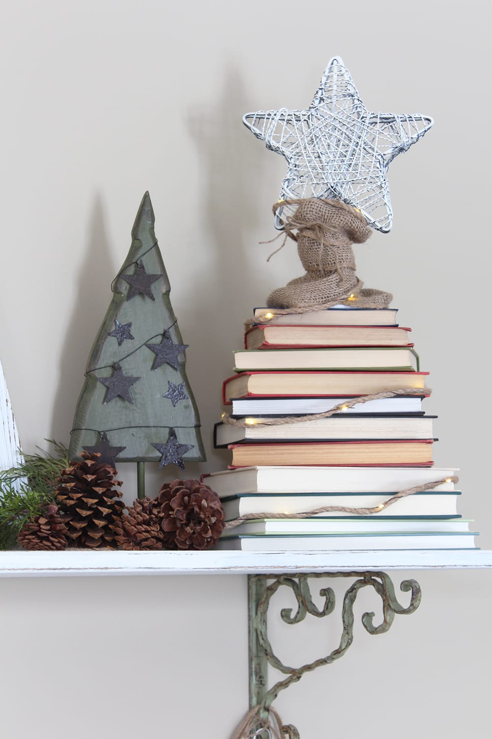 Nature inspired holiday decor alongside a Christmas tree made from a stack of books. For the book nerd in all of us!