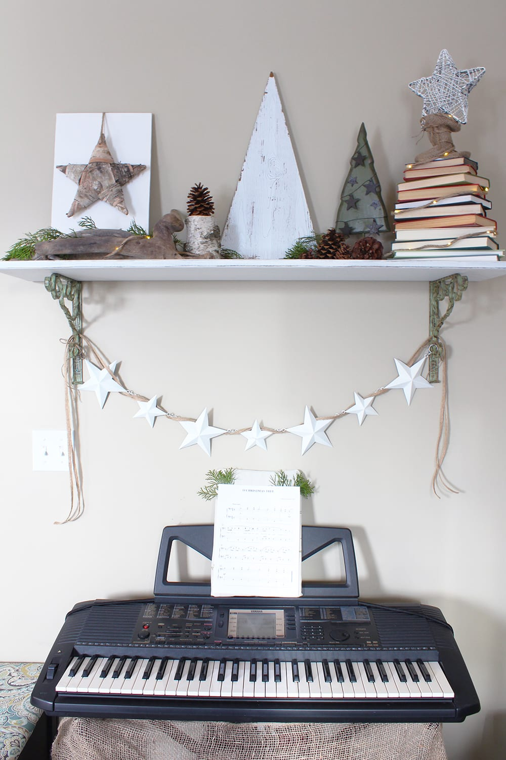 Nature inspired holiday decor featuring driftwood, a birch bark star and a Christmas tree made out of a stack of books.