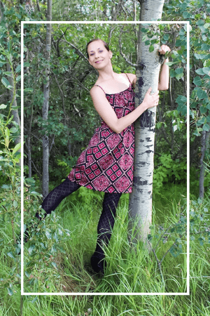Larissa Swayze in a patterned dress hugging a tree. Click to visit the Of Houses and Trees about page.