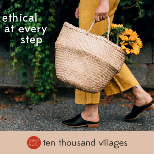 A person walking holding a basket of flowers. Click here to visit Ten Thousand Villages.