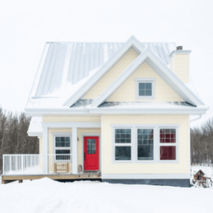 Yellow house with a red door in winter.