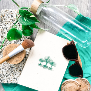 Various eco-friendly items - such as a glass water bottle and wooden sunglasses on a green fabric background.