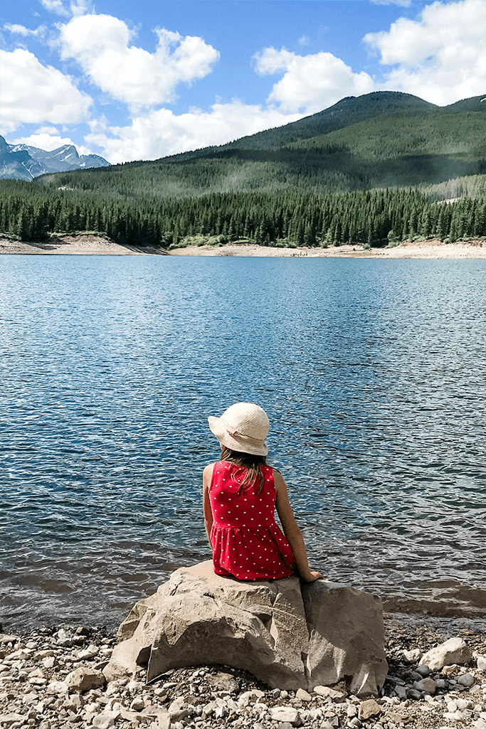 A little girl sitting by a mountain lake.