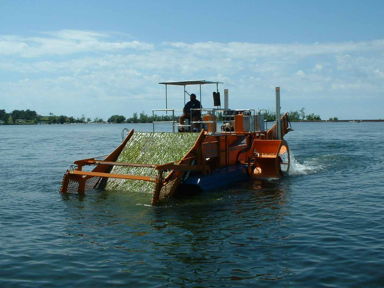 Alphaboats FX-11 Waterweed Harvester rolling weeds up its wide cutting conveyor