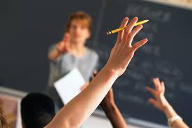Teacher Standing In Front Of Classroom Calling On Student Raising Hand
