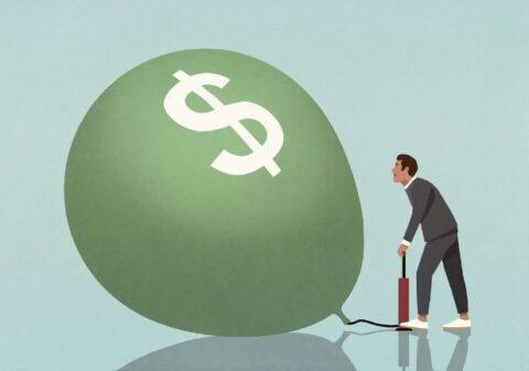Man Inflating Dollar Balloon