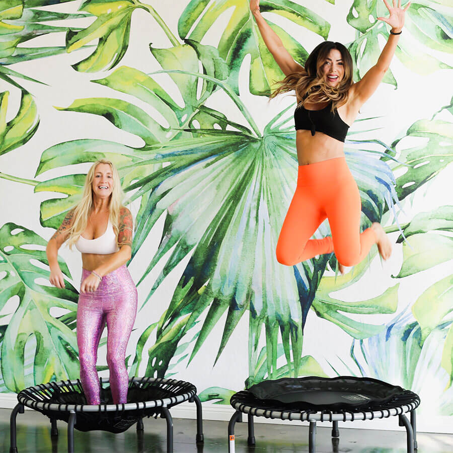 three ladies dressed in workout attire smiling together jumping on trampoline