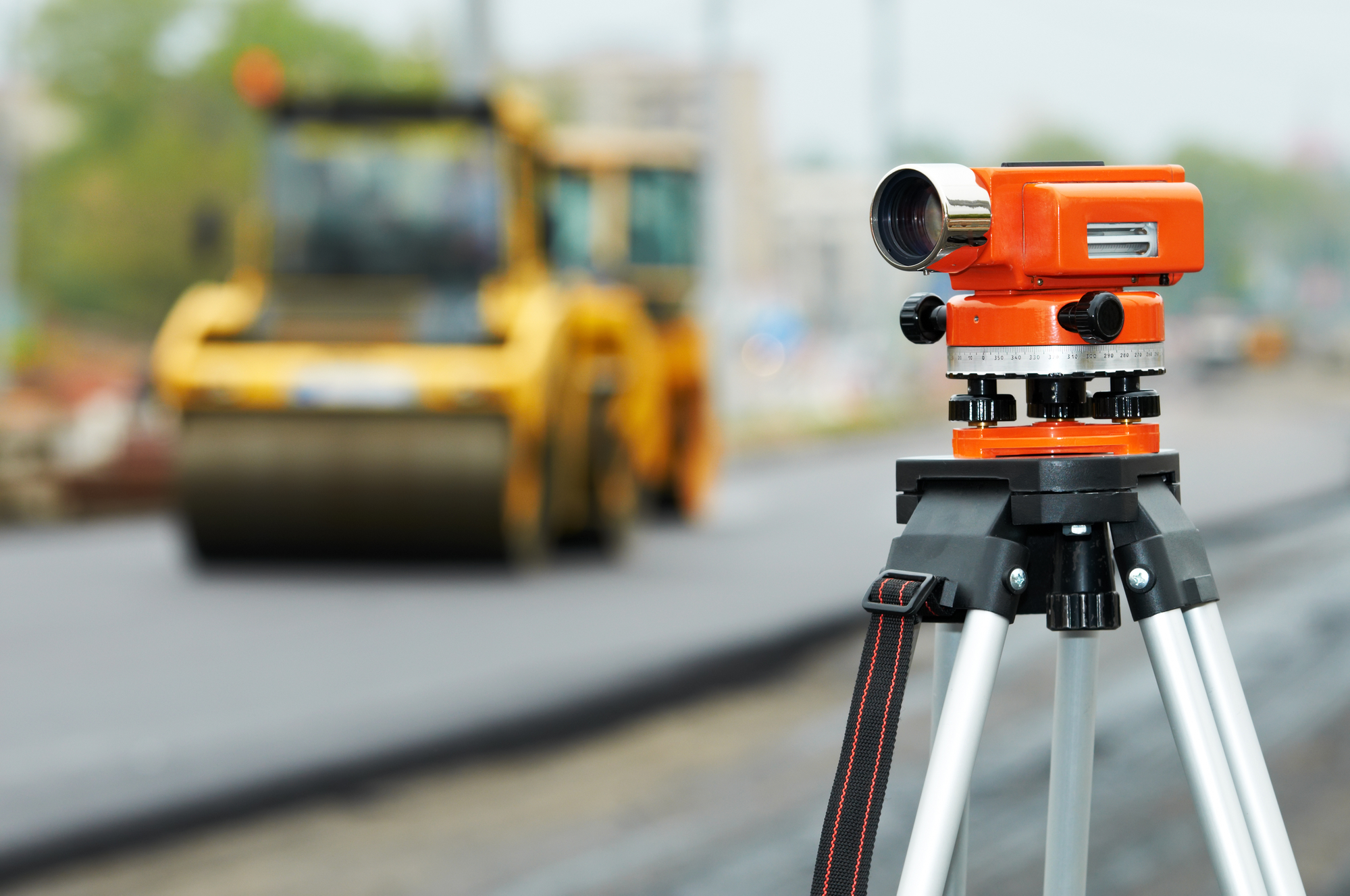 Construction surveyor equipment theodolite level tool during asphalt paving works with compactor roller at background