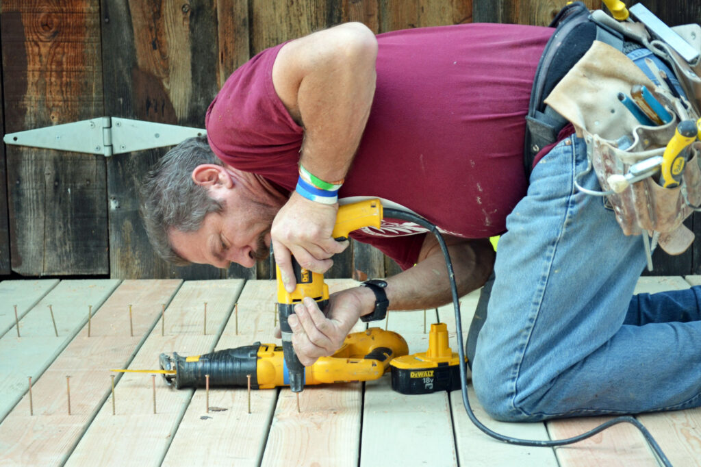 man screwing down boards for deck