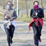 two female runners wearing face masks and social distancing
