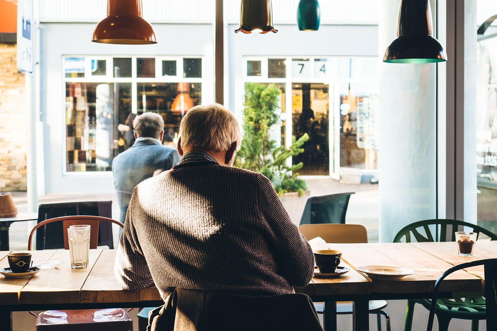 A senior citizen sitting at a coffee shop.