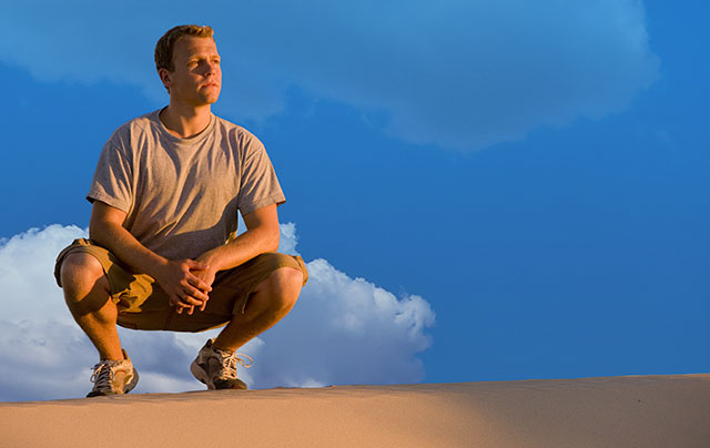 Young man looking out from the top of a sand dune