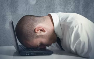 Photo of frustrated man with head on laptop