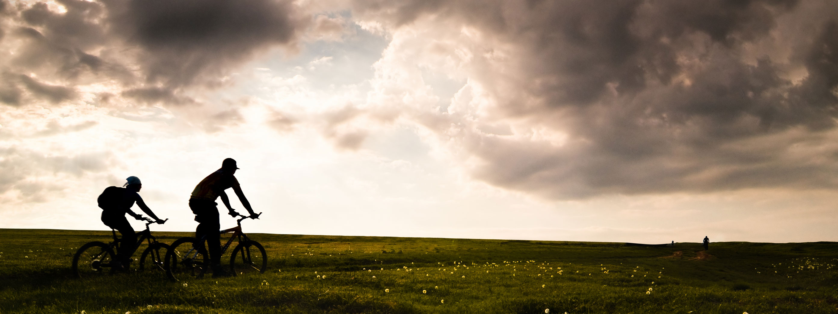 Two people riding bikes in a field