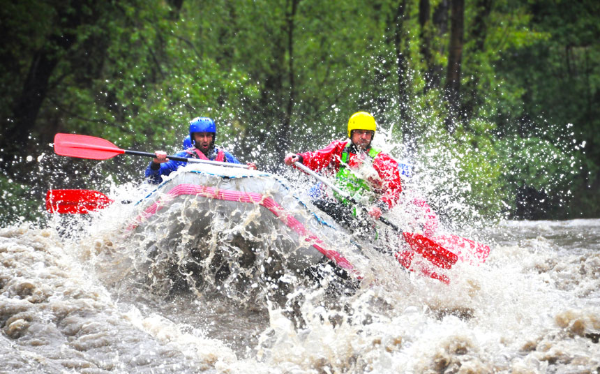 two men riding a wave while white-water rafting
