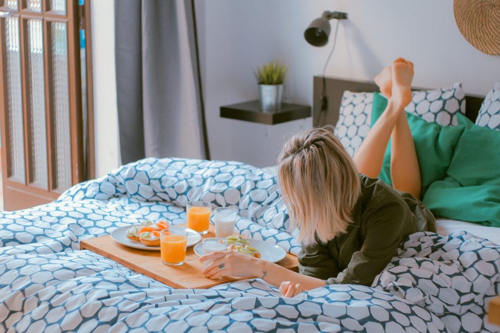 woman eating breakfast on the bed