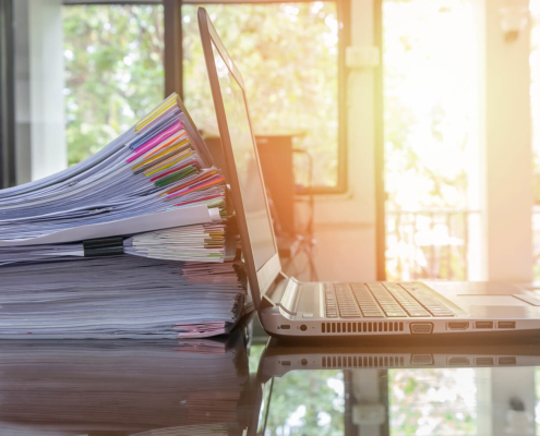 Document Management Software laptop and document stack on office desk with sun flare