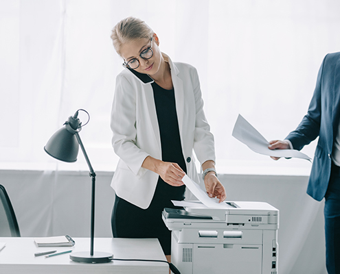 Why Choose Lang Company businesswoman talking on smartphone while using printer in office with colleague near by