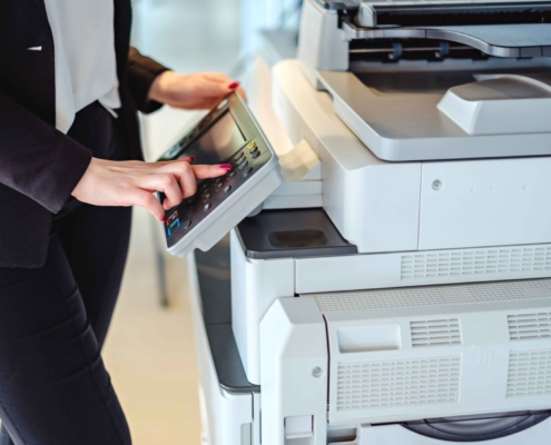 Testimonials Woman pressing button on a copy machine in the office