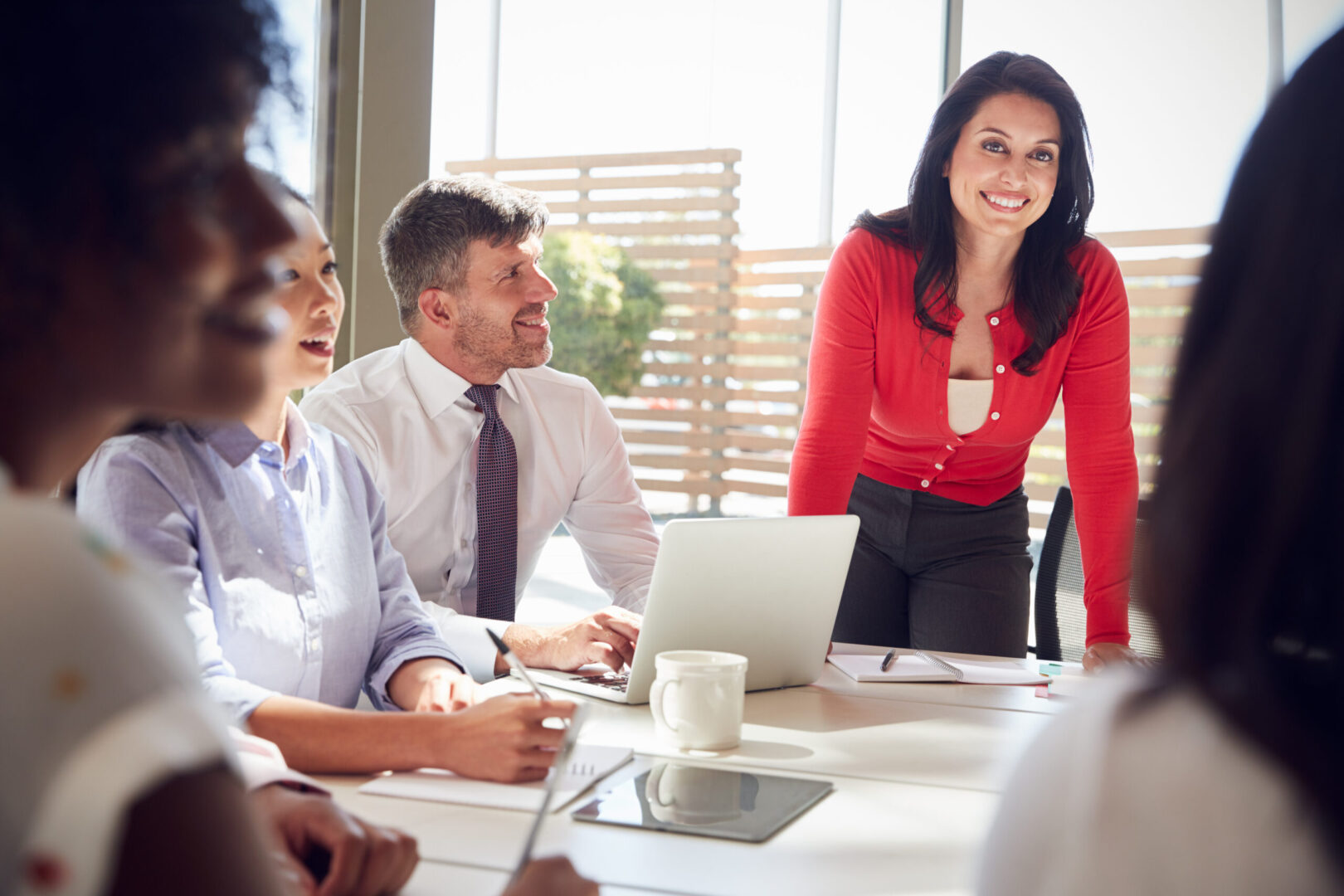 Hispanic businesswoman listening to colleagues at a meeting
