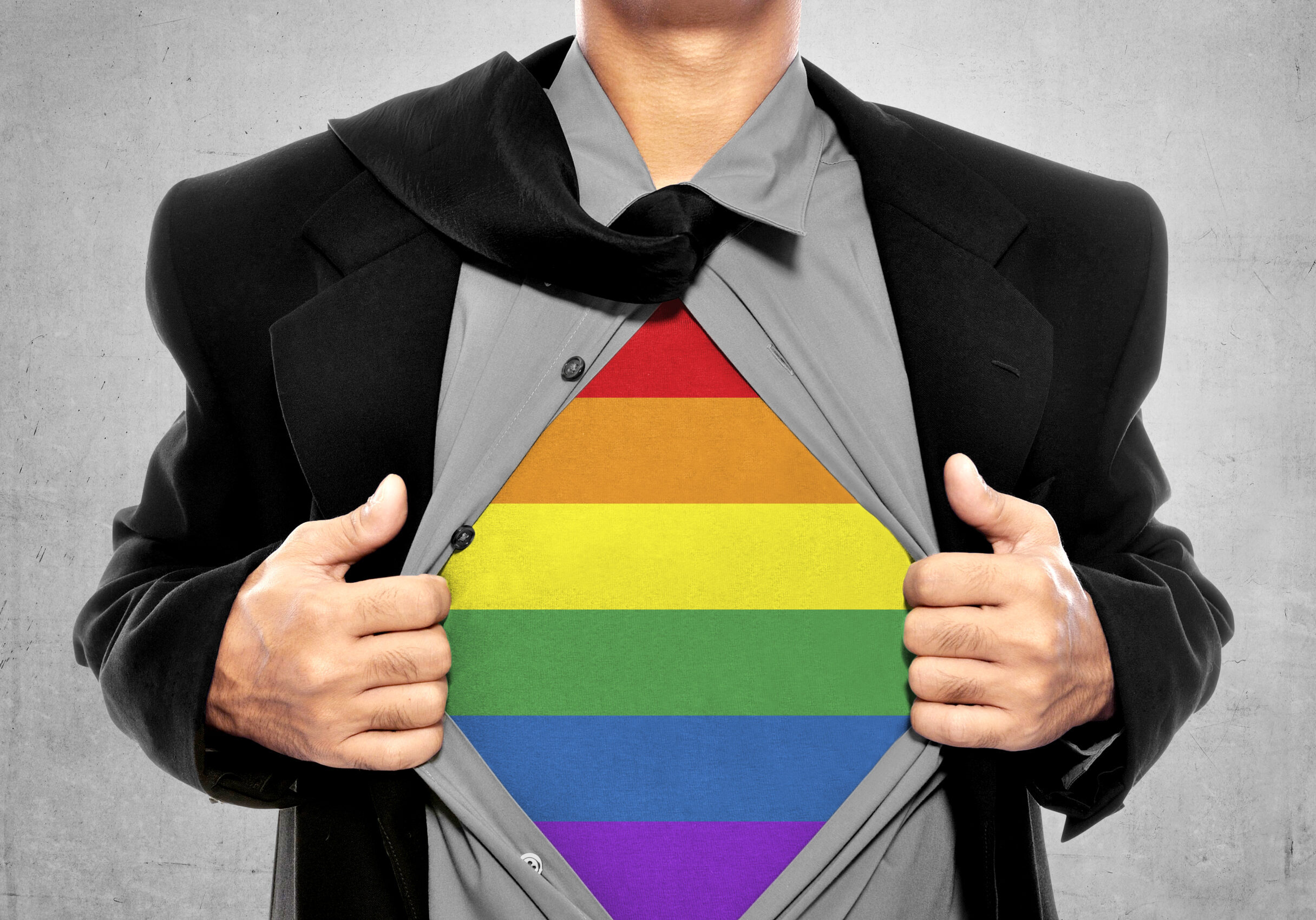 Business man tears open his shirt in a super hero fashion getting ready to save the day. LGBT freedom conceptual