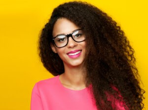 Beautiful young happy african american woman with amazing toothy smile. Girl looking at camera, wearing eyeglasses. Girl with long healthy curly hair. Studio shot.