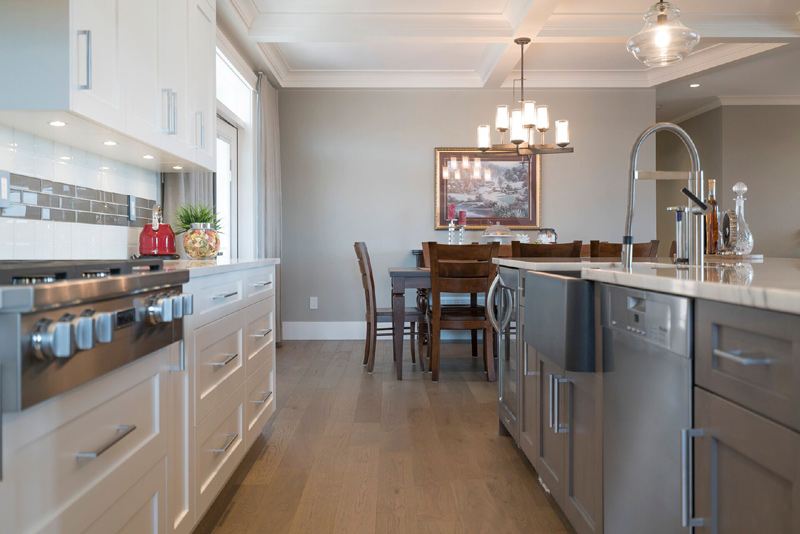 Bright open space kitchen area to work in with a farmhouse style sink surrounded by Calcutta marble.The surrounding countertops finished with a white quartz.