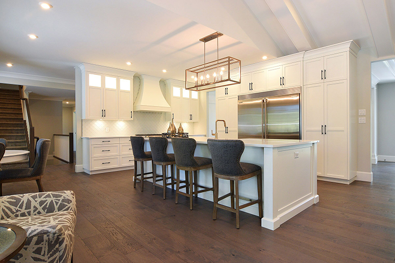 Combining old with new I used modern lighting fixtures with more traditional leather barstools and warm wood flooring that compliment the clean honest lines of this home.