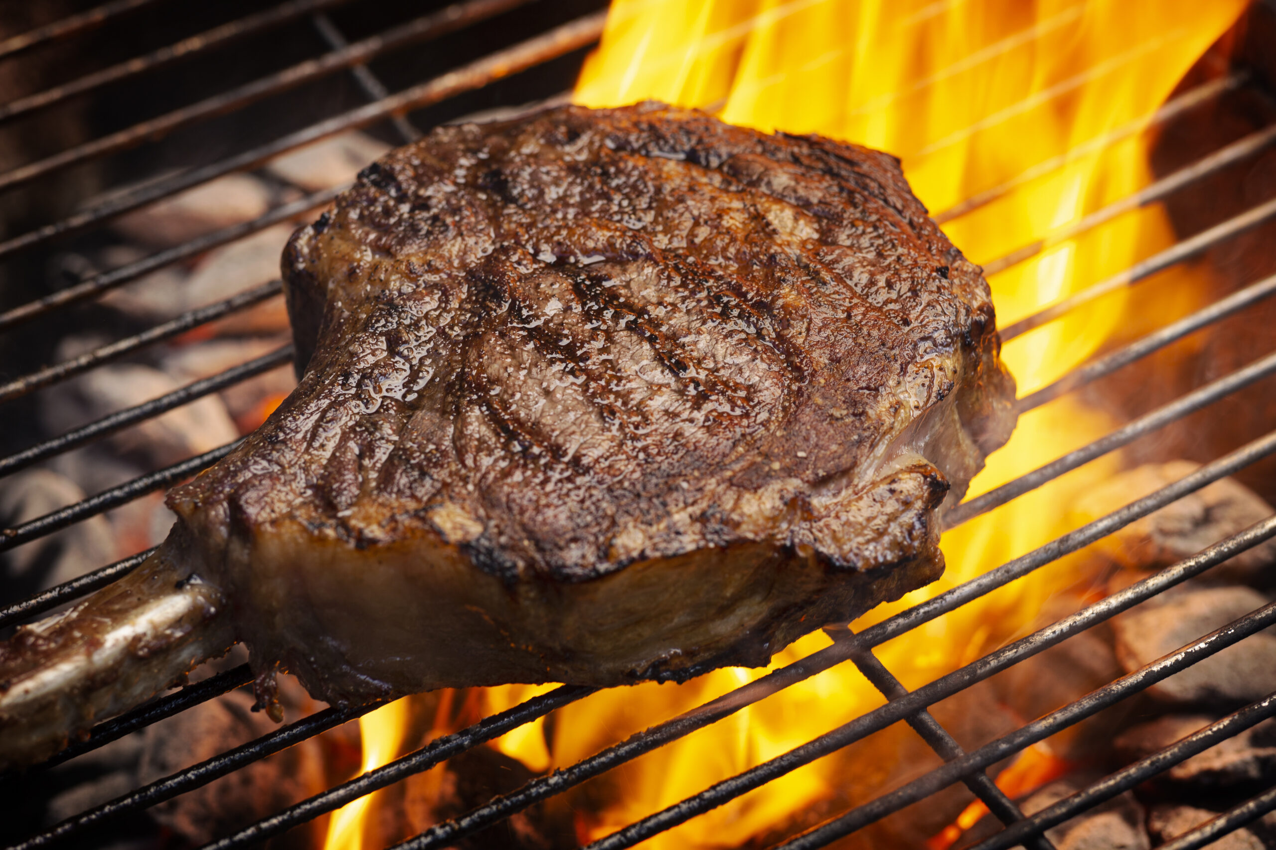 a bone-in tomahawk ribeye steak cooking on grill with flames, angled view