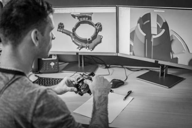 Engineer holding a machine part while making a 3D model on the computer.