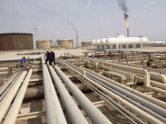 Iraq workers walk on pipelines of an oil refinery - EnergyNewsBeat