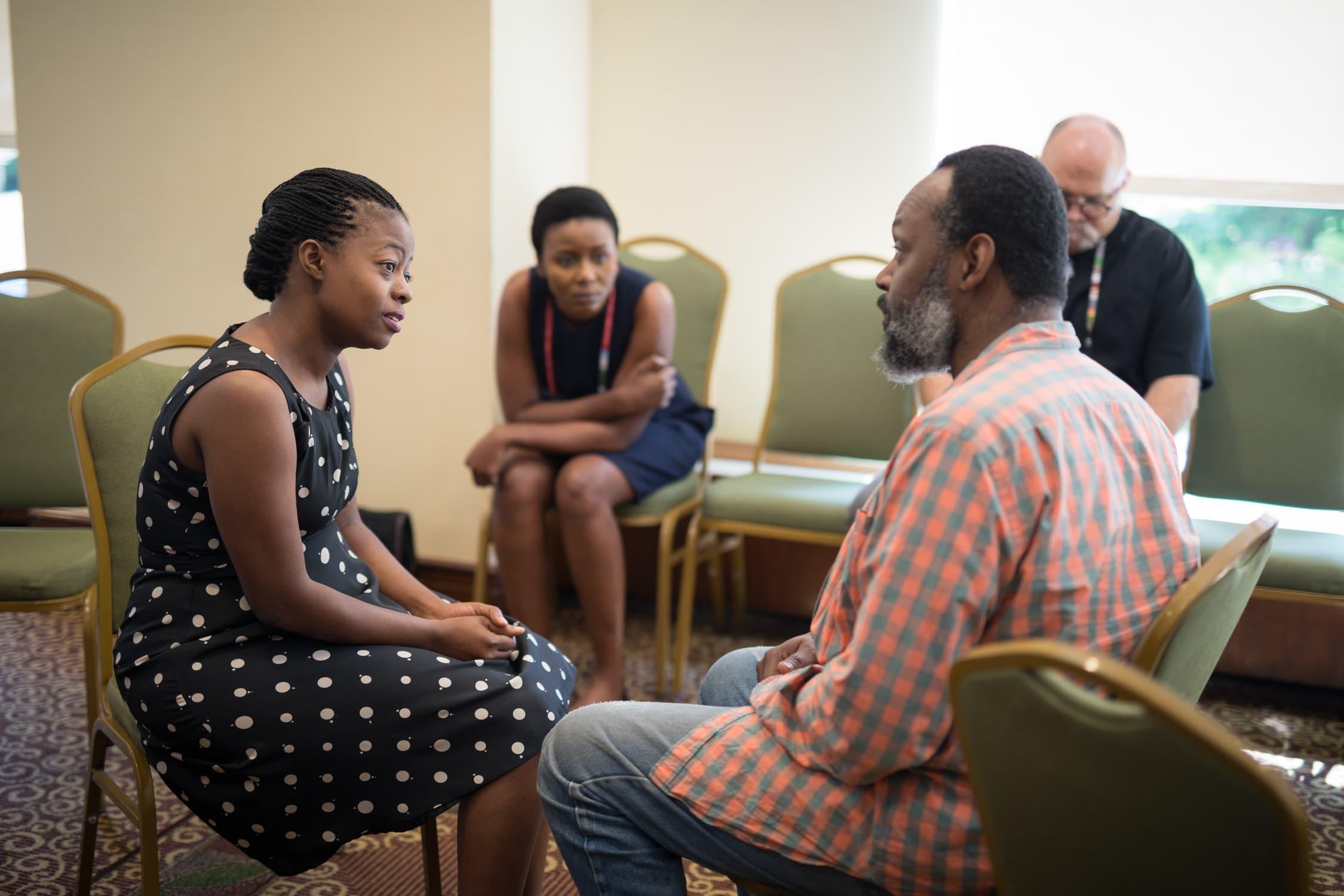 Une femme en robe noire et un homme en chemise orange se parlent, assis sur des chaises l'un en face de l'autre. Une autre femme les regarde.