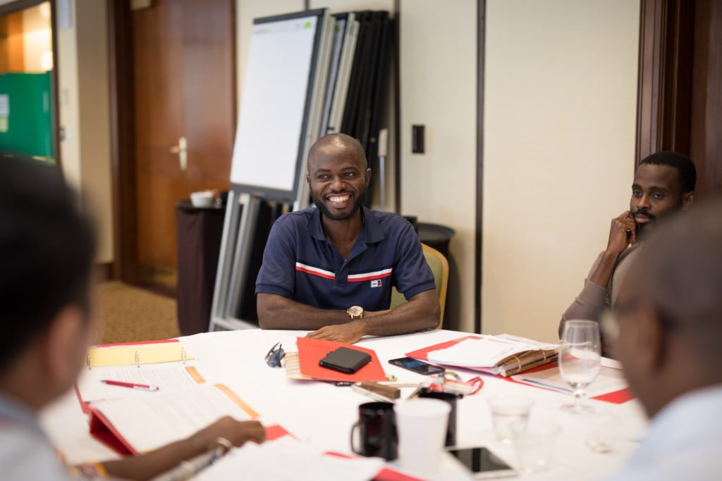 Four people sit around a table with binders open in front of them. A man in a blue shirt smiles at the person next to him.