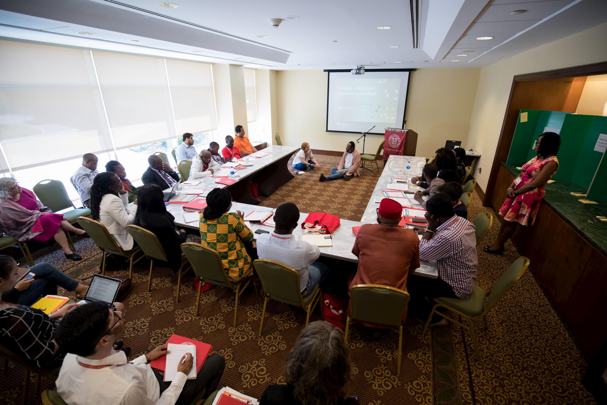 Plusieurs personnes sont assises autour d'une table dans une salle de réunion. Toutes regardent un homme et une femme qui sont assis par terre à l'avant de la salle.